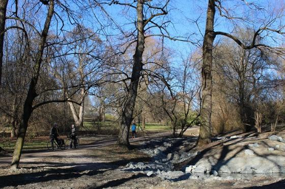 Bilde av parklandskap med trær og bekk.