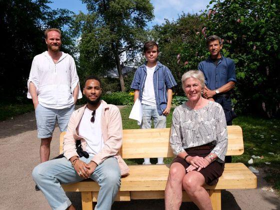 De fem paneldeltagerne sittende på og stående bak Linné-benken i Botanisk hage.