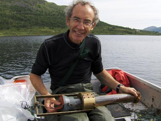 Bilde av forsker i båt med utstyr for å ta prøver av sedimenter.