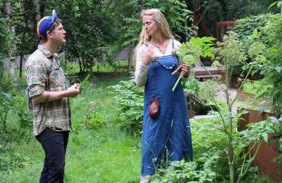 Bilde av mann og kvinne i vikingdrakt med blader av kvann.