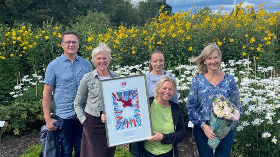 Representanter fra Naturhistorisk museum mottar pris foran et hageanlegg i Botanisk hage